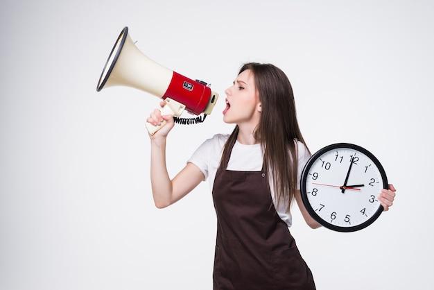 Portret młodej kobiety trzymającej okrągły zegar, krzyk w megafon na białym tle.