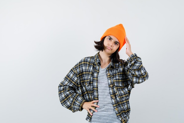 Portret młodej kobiety trzymającej palce na głowie w pomarańczowym kapeluszu wyglądającej na zamyśloną