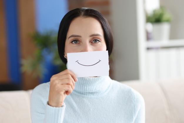 Portret młodej kobiety trzymającej papier z malowanym uśmiechem. dobry nastrój i pozytywna koncepcja