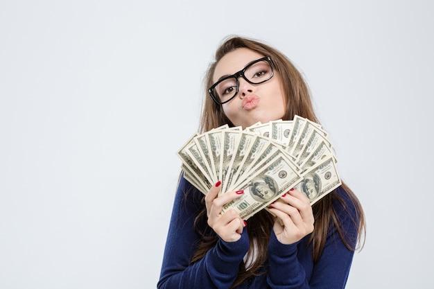 Portret młodej kobiety trzymającej rachunki dolarowe i całującej się w aparacie na białym tle na białym tle