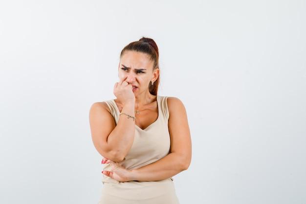 Portret młodej kobiety trzymającej rękę na brodzie w beżowym podkoszulku bez rękawów i patrząc przestraszony widok z przodu