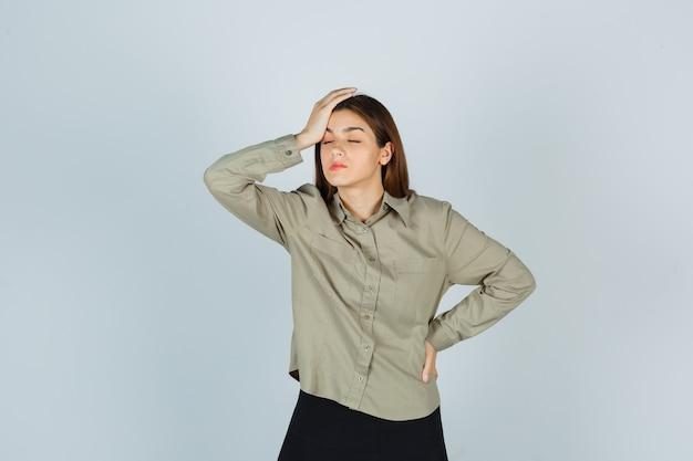 Portret młodej kobiety trzymającej rękę na głowie w koszuli, spódnicy i wyglądającej na zmęczonego widoku z przodu