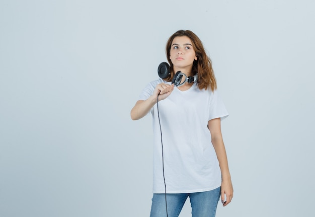 Portret młodej kobiety trzymającej słuchawki myśląc w biały t-shirt, dżinsy i patrząc uroczy widok z przodu