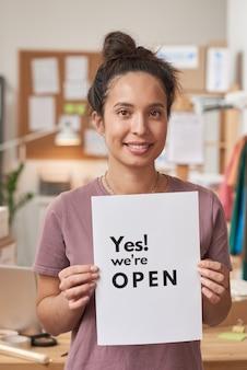 Portret młodej kobiety trzymającej tabliczkę w dłoniach i uśmiechając się z przodu ona otwierając swój biznes