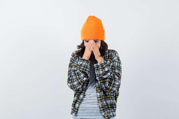 Portret młodej kobiety trzymającej twarz z dłońmi w pomarańczowym kapeluszu i kraciastej koszuli