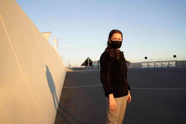 Portret młodej kobiety ubranej w czarny sweter z maską przed szarą ścianą