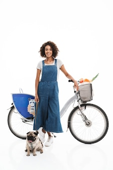 Portret młodej kobiety ubranej w dżinsowe kombinezony z mopsem i rowerem na białym tle nad białą ścianą
