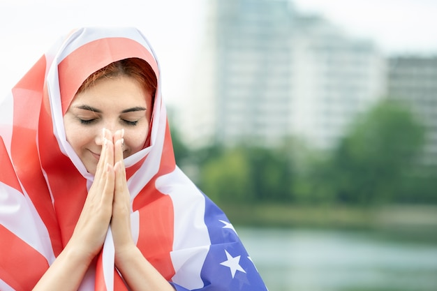 Portret młodej kobiety uchodźcy z flagą narodową usa na głowie i ramionach. pozytywna muzułmańska dziewczyna modli się na zewnątrz.