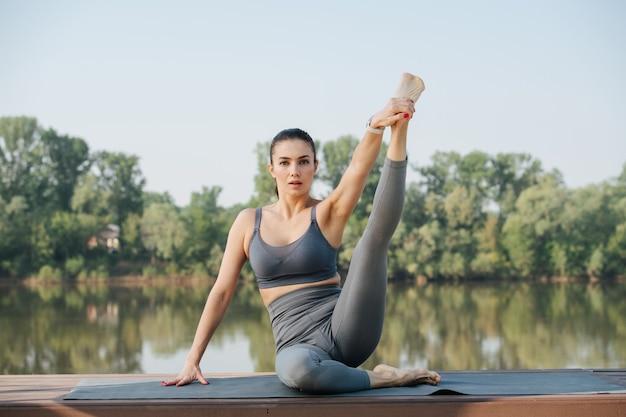 Portret młodej kobiety uprawiającej jogę na świeżym powietrzu w pięknym miejscu nad rzeką