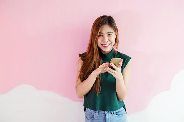 Portret młodej kobiety, uśmiech podczas korzystania z inteligentnego telefonu