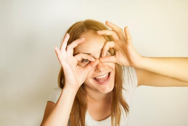 Portret młodej kobiety, uśmiecha się do kamery.
