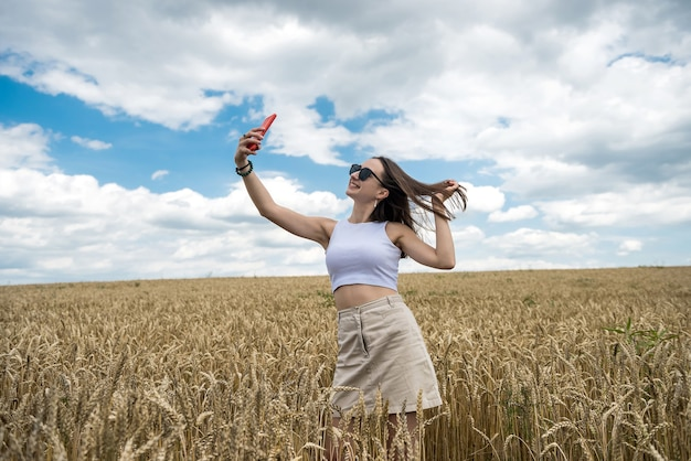 Portret młodej kobiety uśmiechający się stojący w polu pszenicy. wolna szczęśliwa dziewczyna