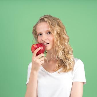 Portret młodej kobiety uśmiechnięta bitting czerwone jabłko na zielonej ścianie. świeża twarz
