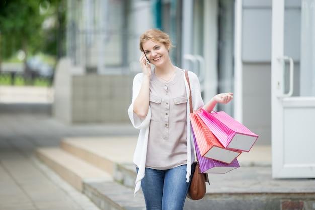 Portret młodej kobiety uśmiechnięta na telefon komórkowy podczas czasu zakupów