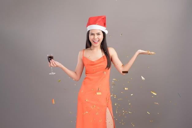 Portret młodej kobiety uśmiechnięta ubrana w czerwony kapelusz świętego mikołaja trzyma kieliszek wina