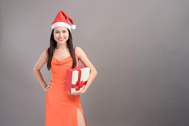 Portret młodej kobiety uśmiechnięta ubrana w czerwony kapelusz świętego mikołaja trzyma pudełko