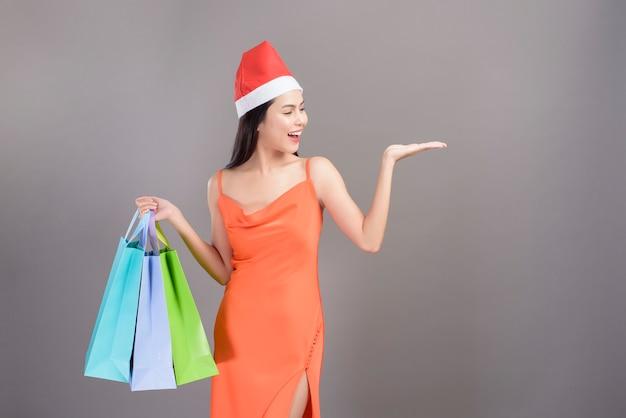 Portret młodej kobiety uśmiechnięta ubrana w czerwony kapelusz świętego mikołaja trzyma torby na zakupy