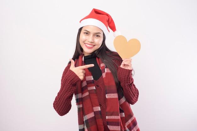 Portret młodej kobiety uśmiechnięta ubrana w czerwony kapelusz świętego mikołaja