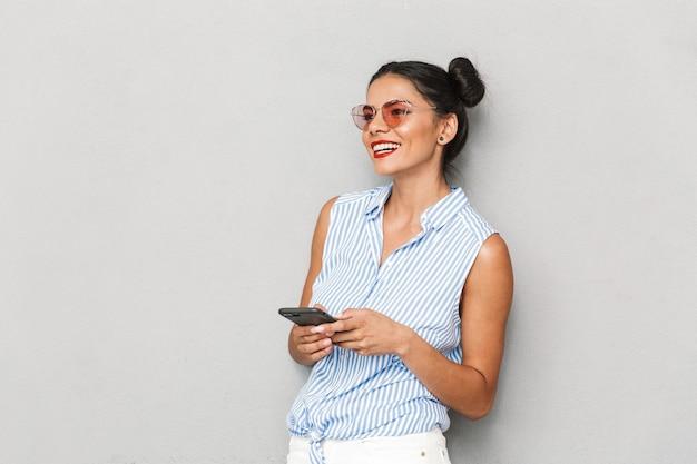 Portret młodej kobiety uśmiechnięta w okulary odizolowane, przy użyciu telefonu komórkowego
