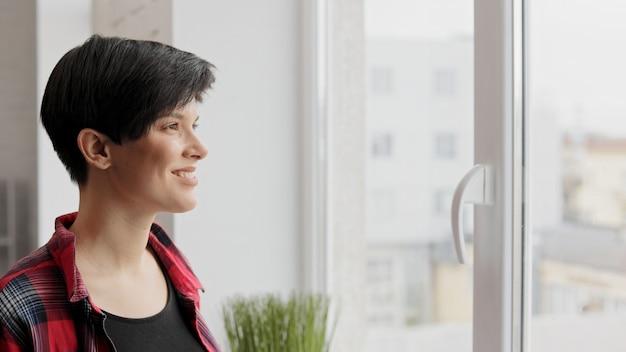Portret młodej kobiety uśmiechnięte, patrząc w okno