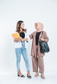 Portret młodej kobiety uśmiechnięte spotkanie z przyjacielem badania, niosąc torbę i książkę na białym tle