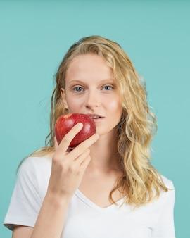 Portret młodej kobiety uśmiechnięte z czerwonym jabłkiem. świeża twarz, naturalne piękno, realistyczne. oczyść młodą, świeżą skórę bez makijażu i retuszu.