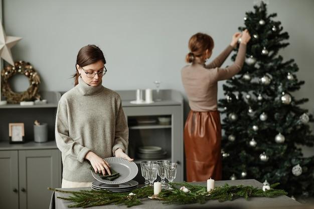 Portret młodej kobiety ustawiającej talerze na stole udekorowanym na boże narodzenie gałązkami jodły ...