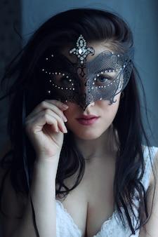 Portret młodej kobiety uwodzicielskiej w czarnej masce karnawałowej