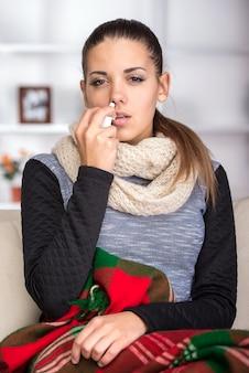 Portret młodej kobiety używa spray do nosa.