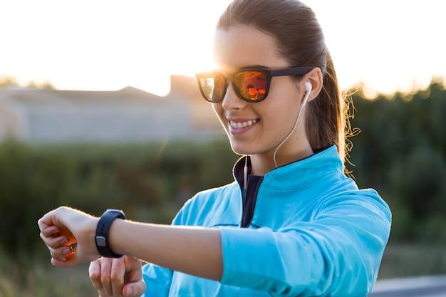Portret młodej kobiety, używając smartwatch po uruchomieniu.
