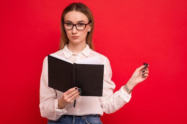 Portret młodej kobiety w białej koszuli, która pisze w pamiętniku na czerwonym tle