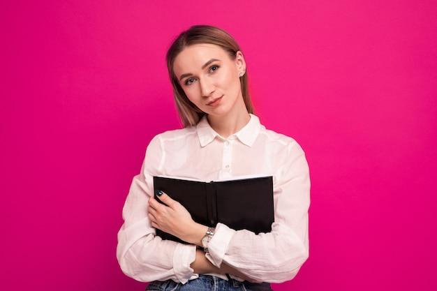 Portret młodej kobiety w białej koszuli, która pisze w pamiętniku na różowym tle