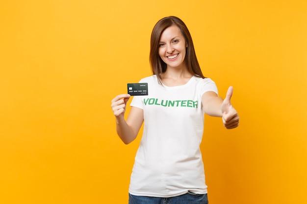 Portret młodej kobiety w białym t-shirt z napisem zielony tytuł wolontariusz trzymać kartę kredytową bank na białym tle na żółtym tle. dobrowolna bezpłatna pomoc pomoc, koncepcja pracy łaski charytatywnej.