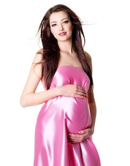 Portret młodej kobiety w ciąży glamourbeautiful na białym tle