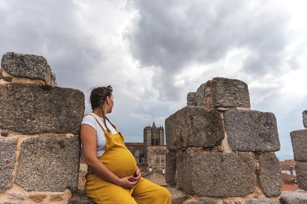 Portret młodej kobiety w ciąży, patrząc w kierunku katedry w avila.