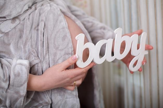"""Portret młodej kobiety w ciąży w pięknej bieliźnie w sypialni. drewniany napis """"baby"""". 9 miesięcy w ciąży z bliska"""