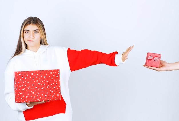 Portret młodej kobiety w ciepłej bluzie z kapturem stojącej w pobliżu prezentu świątecznego