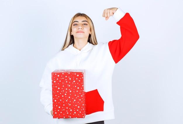 Portret młodej kobiety w ciepłym swetrze z prezentem świątecznym pokazującym mięśnie