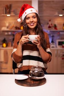 Portret młodej kobiety w czapce świętego mikołaja i uśmiechniętej