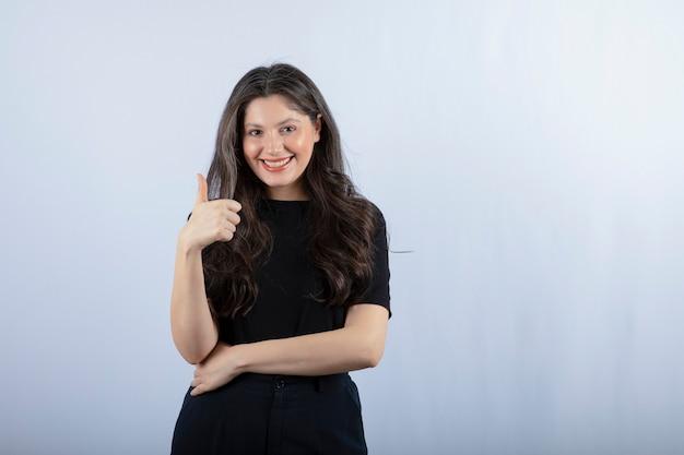 Portret młodej kobiety w czarnym stroju odstawiającym kciuki do góry.