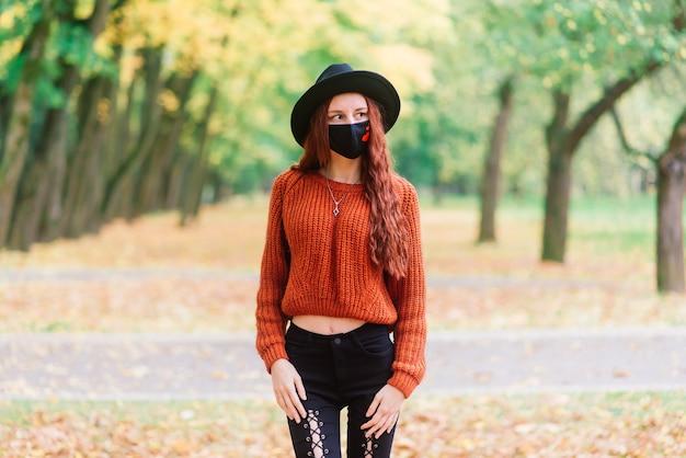 Portret młodej kobiety w czerwony sweter z dzianiny, kapelusz w czarnej stylowej masce medycznej w jesiennym parku żółtym. moda, styl życia, kwarantanna, koronawirus.
