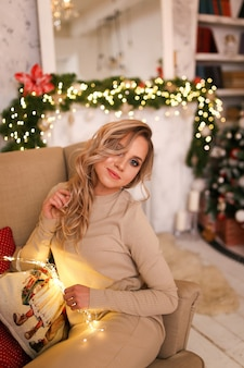 Portret młodej kobiety w domowej sukience i ciepłych skarpetkach relaksuje się przy kominku i choince