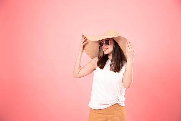 Portret młodej kobiety w dużym kapeluszu letnim i okularach przeciwsłonecznych