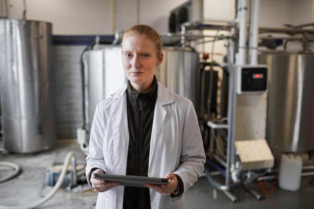 Portret młodej kobiety w fartuchu laboratoryjnym pozuje do maszyn podczas pracy w fabryce mleczarskiej w pasie