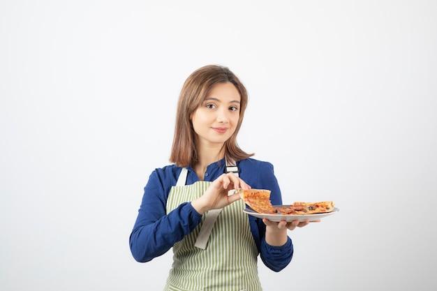 Portret młodej kobiety w fartuchu pokazujący plasterki pizzy na białym tle