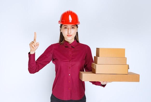 Portret młodej kobiety w kasku z papierowymi pudełkami wskazującym palcem w górę.
