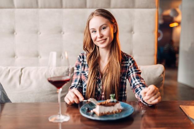 Portret młodej kobiety w kawiarni, słodkie ciasto i czerwone wino w szklance na stole. dziewczyna z czekoladowym deserem w restauracji