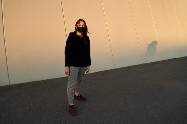 Portret młodej kobiety w kolorze czarnym na sobie maskę przed szarej ściany