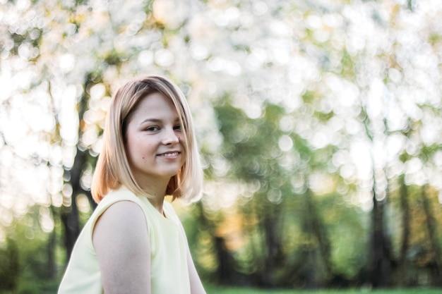 Portret młodej kobiety w letnim parku