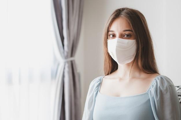 Portret młodej kobiety w masce medycznej chroniącej przed koronawirusem przebywa w domu podczas kwarantanny